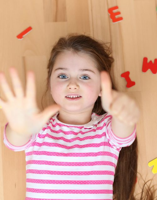 Portrait of six years old child ready showing six fingers - ready for school